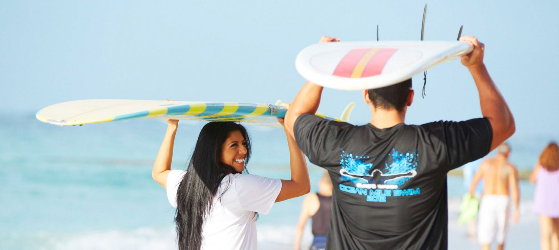 Friends carrying surfboards above their heads