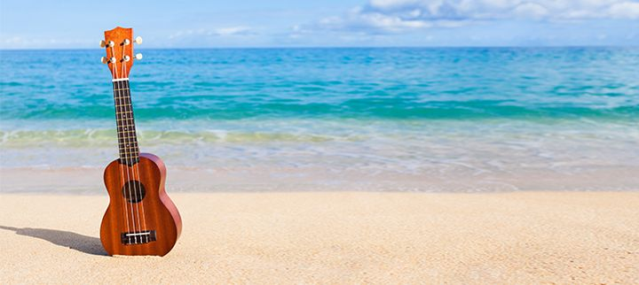 Ukelele laying on the beach with water in the background